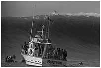 Judging boat with huge wave and surfer at crest. Half Moon Bay, California, USA ( black and white)