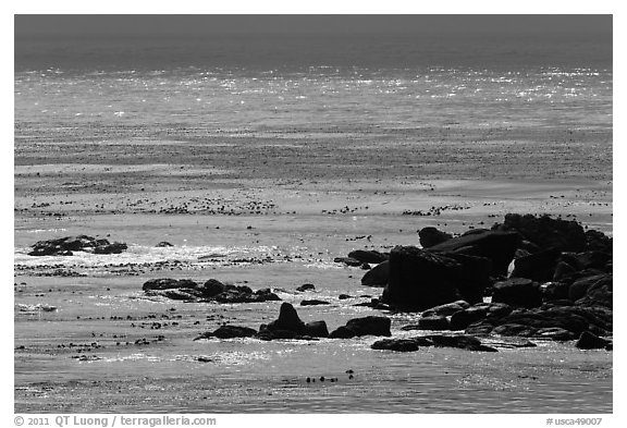 Rocks and backlit water, Carmel Bay. Carmel-by-the-Sea, California, USA