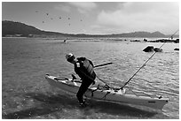 Man boards sea kayak, Carmel Bay. Carmel-by-the-Sea, California, USA (black and white)