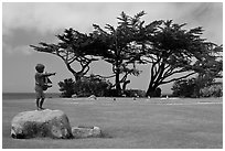 Sculpture, lawn, and cypress, Lovers Point Park. Pacific Grove, California, USA (black and white)