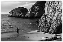Boy standing at the base of bluff, China Cove. Point Lobos State Preserve, California, USA ( black and white)