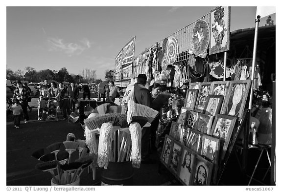 Brooms and religious pictures for sale, San Jose Flee Market. San Jose, California, USA (black and white)