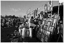 Brooms and religious pictures for sale, San Jose Flee Market. San Jose, California, USA ( black and white)