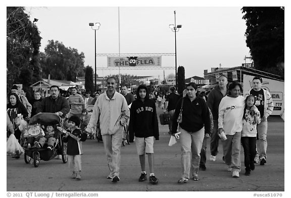 Families walking with entrance sign behind, San Jose Flee Market. San Jose, California, USA (black and white)