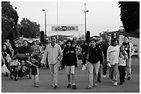 Families walking with entrance sign behind, San Jose Flee Market. San Jose, California, USA ( black and white)