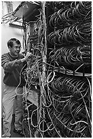 Man with tangle of wires in server room. Menlo Park,  California, USA (black and white)