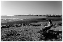 Woman sitting on bench, Carquinez Strait Regional Shoreline. Martinez, California, USA ( black and white)