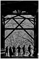 Silhouettes of people dancing inside covered bridge, Felton. California, USA ( black and white)
