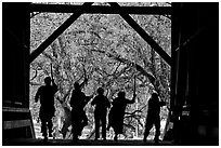Silhouettes of dancers with sticks inside covered bridge, Felton. California, USA ( black and white)