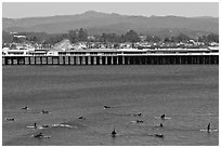 Surfers and municipal wharf. Santa Cruz, California, USA (black and white)