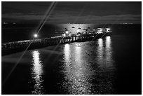 Wharf with moon reflections and light rays. Capitola, California, USA (black and white)