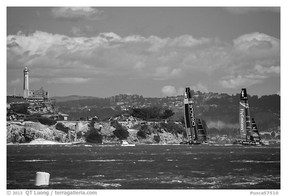 America's cup boats sail away at 40 knots from Alcatraz Island. San Francisco, California, USA (black and white)