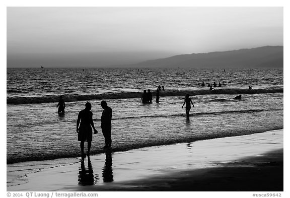 Sunset with beachgoers in water. Santa Monica, Los Angeles, California, USA (black and white)