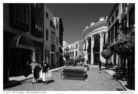 People carry garnments in  Rodeo Drive shopping district. Beverly Hills, Los Angeles, California, USA (black and white)