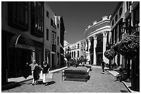 People carry garnments in  Rodeo Drive shopping district. Beverly Hills, Los Angeles, California, USA ( black and white)