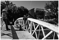 Boy fishing from arched bridge, Venice Canal Historic District. Venice, Los Angeles, California, USA ( black and white)