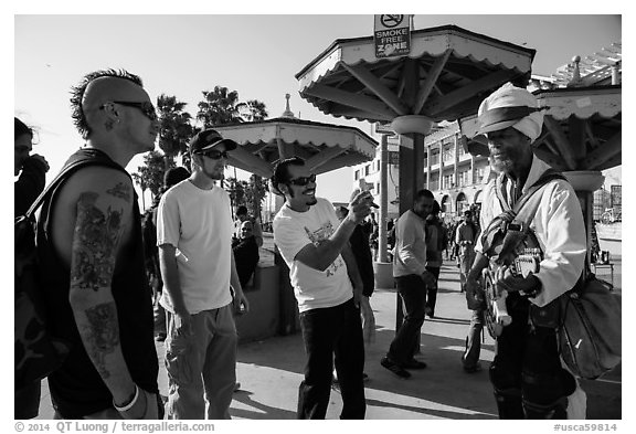 Tourists photograph Ocean Front Walk entertainer. Venice, Los Angeles, California, USA (black and white)
