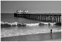 Man fishing next to Malibu Pier. Los Angeles, California, USA ( black and white)