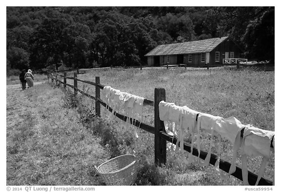 Laundry drying on fence, as elderly couple in period costume walks in distance, Fort Tejon. California, USA (black and white)