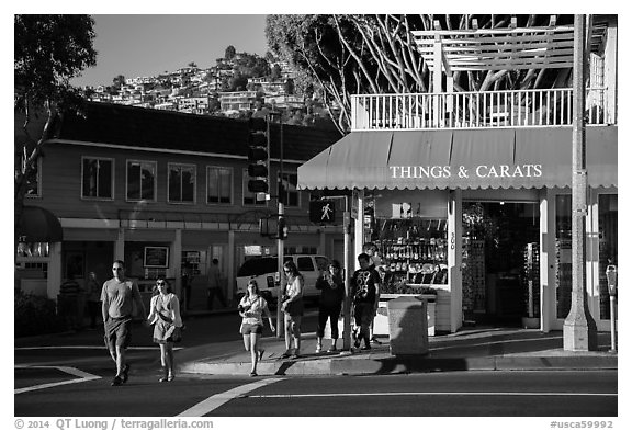 Visitors cross street in shopping area. Laguna Beach, Orange County, California, USA (black and white)