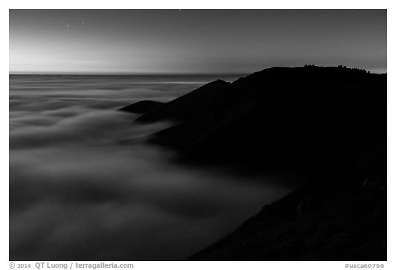 Hills emerging from sea of clouds at dusk, Garrapata State Park. Big Sur, California, USA (black and white)
