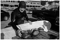 Man with surfboard examining abalone. California, USA ( black and white)