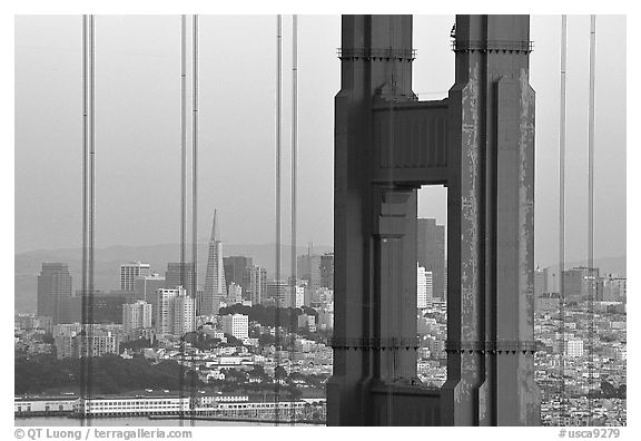 City through cables and pilars of Golden Gate bridge, dusk. San Francisco, California, USA (black and white)