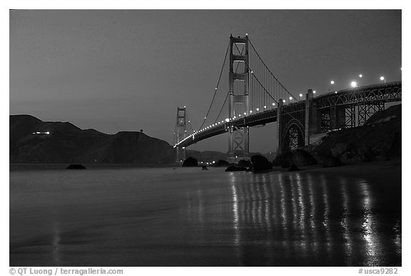 Golden Gate bridge and surf with light reflections, seen from E Baker Beach, dusk. San Francisco, California, USA (black and white)
