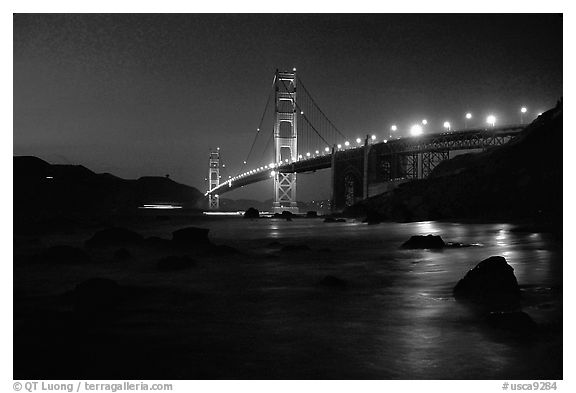 Golden Gate bridge and surf seen from E Baker Beach, night. San Francisco, California, USA (black and white)