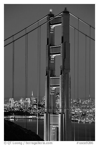 The city seen through the cables and pilars of the Golden Gate bridge, night. San Francisco, California, USA (black and white)