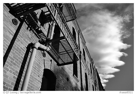Old brick building and serrated cloud, sunset, Fisherman's Wharf. San Francisco, California, USA (black and white)