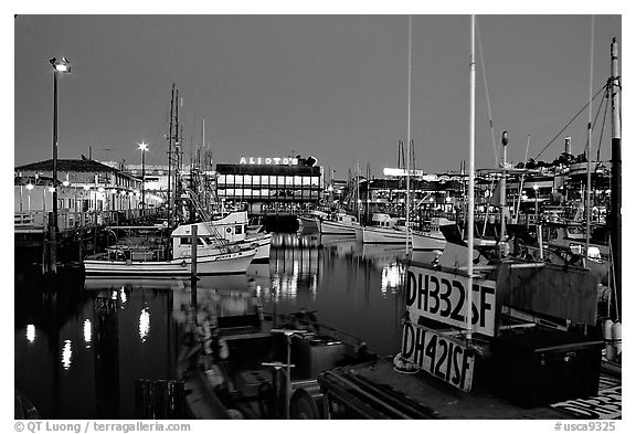 Fishing boat in  Fisherman's Wharf, with Alioto's in the background, dusk. San Francisco, California, USA (black and white)