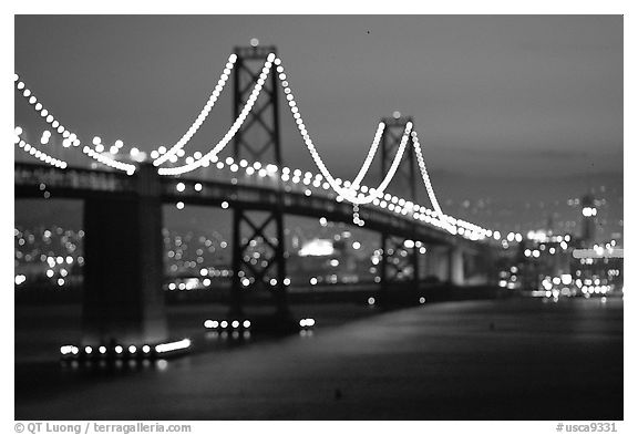 Bay Bridge seen from Treasure Island with defocused lights, sunset. San Francisco, California, USA (black and white)