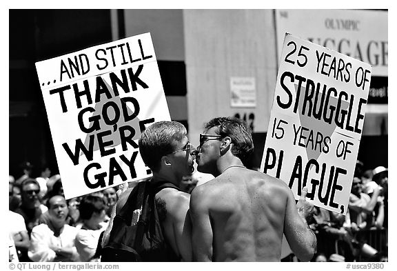 Gay couple with signs during the Gay Parade. San Francisco, California, USA (black and white)