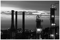 Chimneys of industrial Oil Refinery near Rodeo at sunset. SF Bay area, California, USA ( black and white)