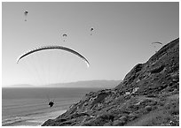Paragliders soaring above cliffs, the Dumps, Pacifica. San Mateo County, California, USA ( black and white)