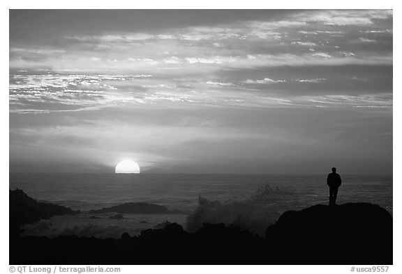 Man watching sunset over ocean. Pacific Grove, California, USA (black and white)