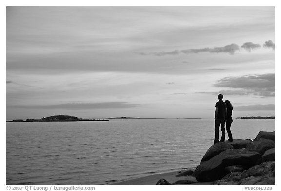 Couple standing on rock and Atlantic Ocean at sunset, Westbrook. Connecticut, USA