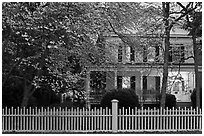 White picket fence, dogwoods, and house at dusk, Old Lyme. Connecticut, USA ( black and white)