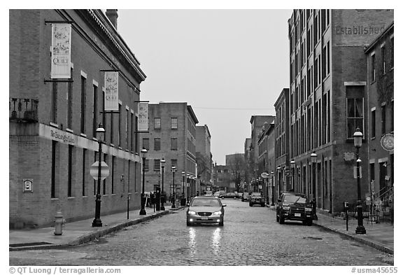 Downtown street lined with brick buildings in the rain, Lowell. Massachussets, USA (black and white)