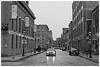 Downtown street lined with brick buildings in the rain, Lowell. Massachussets, USA ( black and white)
