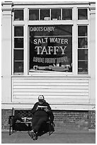 Man reading in front of Salt Water taffy store, Provincetown. Cape Cod, Massachussets, USA (black and white)