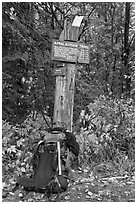 Backpack and marker for last 100 miles, wildest of Appalachian trail. Maine, USA (black and white)