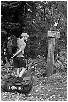 Backpacker shouldering pack at trailhead. Maine, USA (black and white)