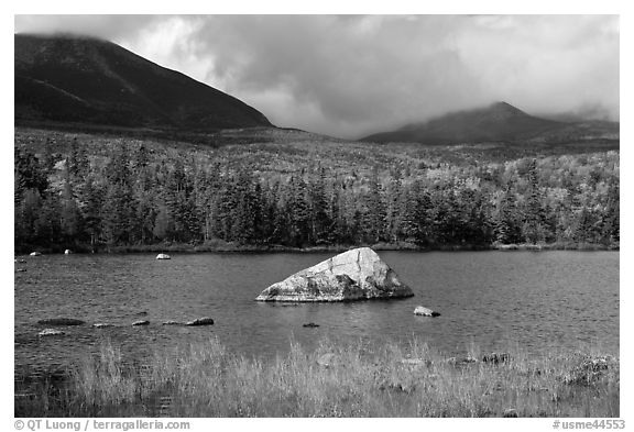 Boulder, pond, forest in autumn and mountains with clouds. Baxter State Park, Maine, USA (black and white)
