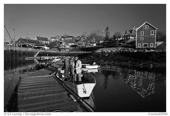 Men preparing to leave on small boat. Stonington, Maine, USA (black and white)