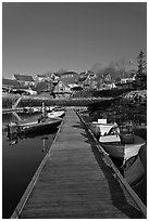 Deck, small boats, and houses. Stonington, Maine, USA (black and white)