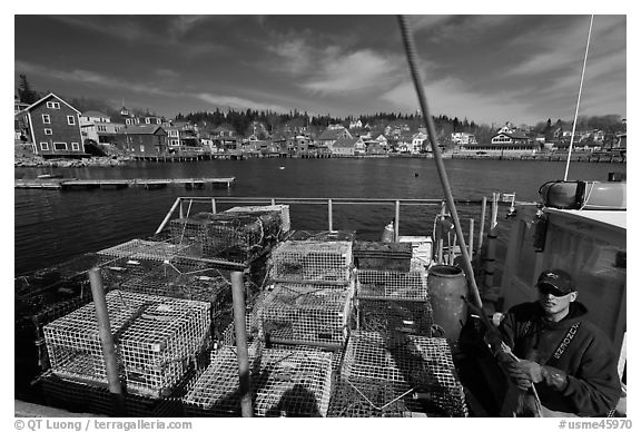Lobsterman in boat with traps, and village in background. Stonington, Maine, USA (black and white)