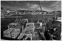 Lobsterman in boat with traps, and village in background. Stonington, Maine, USA ( black and white)