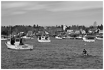 Man paddling to board lobster boat. Corea, Maine, USA (black and white)